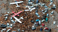 Planes, cars and debris swept away in the tsunami in Sendai (Reuters)