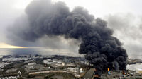 Smoke rises from a burning factory following an earthquake and tsunami in Sendai, northeastern Japan