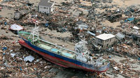 A ship lifted up into a town by a tsunami following an earthquake is seen in Miyagi Prefecture,