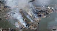 Smoke rises from houses damaged by an earthquake and tsunami in Sendai