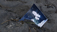 A family photograph is half buried in the mud in Rikuzentakata after it was a destroyed by an 8.9 magnitude earthquake (Reuters)