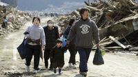 A family walks past buildings destroyed by a tsunami in Minamisanriku, Miyagi Prefecture, in northern Japan