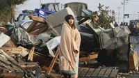 A woman looks at the damage caused by a tsunami and earthquake in Ishimaki City.
