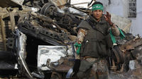 A Libyan army soldier smokes in front of destroyed vehicles near a damaged mosque at Martyr's Square in the centre of Zawiyah (Reuters)