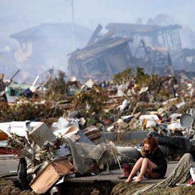 A woman cries while sitting on a road amid the destroyed city of Natori, Miyagi Prefecture in northern Japan (reuters)