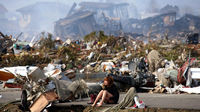 A girl sits amongst the wreckage after the worst earthquake in the history of Japan