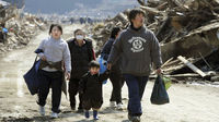 A family in Minamisanriku walks through the rubble and splintered remains of their town