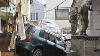 Japan Self-Defence Force troops walk on a wall to get around a car tossed by a tsunami and earthquake in Kesennuma