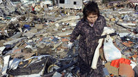 Ofunato resident wades through the wreckage (Reuters)