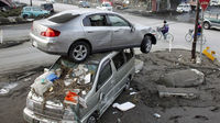 A car sits atop another in an area affected by an earthquake and tsunami in Miyako, Iwate prefecture