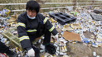 A South Korean rescue worker sits on scattered beer cans as his team stops searching after the radioactive warning
