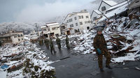 Members of the Japan Self Defence force walk through the snow-covered ruins of Kamaishi