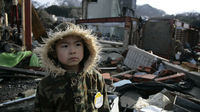 Hirohiko and his son Suzunosuke in the rubble of Onigawa, Japan, see the remains of their home (Save the Children)