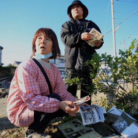 Japan tsunami: a woman sifts through the debris in Asahi (Save the Children)