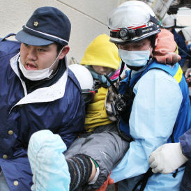Japan: 16-year-old Jin Abe is carried by rescue workers from the rubble in Ishinomaki City (Reuters)