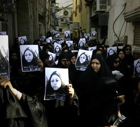 Bahraini women hold placards with the image of the dead woman Bahiya al-Aradi