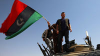 Rebel fighters celebrate by waving a Kingdom of Libya flag on the outskirts of the town of Ajdabiya (Reuters)