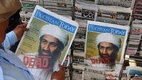 A man reads a newspaper article about Osama bin Laden's death.
