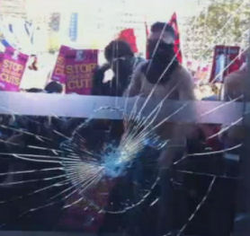 Student tuition fees march: smashed window at Tory HQ.
