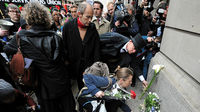 Demonstrators lay flowers on the spot where Ian Tomlinson died during the G20 demonstrations in London (Reuters)