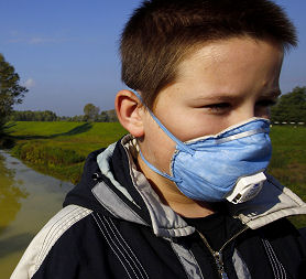 A boy wears a mask next to the Marcal River in Morichida, where a spill has killed fish (Reuters)