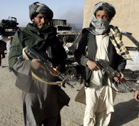 Members of the Taliban pose in front of burnt supply trucks in Ghazni province. (Reuters)