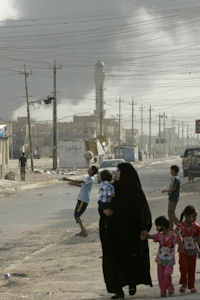 Iraq war files: a woman walks in Sadr City as a Hellfire explodes in the distance. (Reuters)