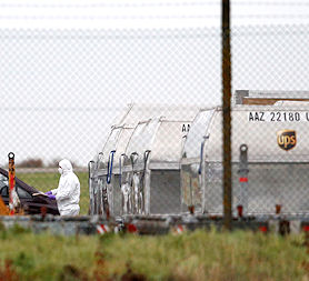 A forensic officer at East Midlands Airport investigates the suspicious package