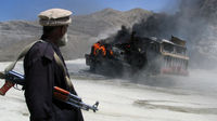 A man looks at a truck set on fire during Taliban fighting. (Reuters)