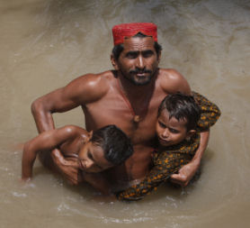 A father with his sons in the flood waters. (Reuters)