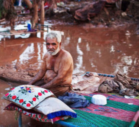 A man sits with his belongings in the mud after the flood. (Getty)