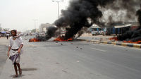 Yemeni man walks past burning tyres during a protest in the southern town of Sabr. (Getty)