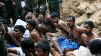 A wider shot of some alleged combatants captured by the Sri Lankan army, whose soldiers stand over the vanquished insurgents.