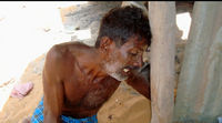 A Tamil man mourns his wife, killed by a mortar in their makeshift home, May 2009.