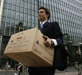 A worker carries a box out of the U.S. investment bank Lehman Brothers in London