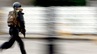 An armed officer running during the Mumbai attacks. (Getty)