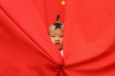 A child wraps themselves in the Chinese flag